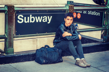 Asian American student traveling in New York, wearing black leather jacket, pants, boot shoes, headphone on neck, duffel bag on ground, sitting on street by Subway sign. Filtered effect..