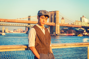 New York City Boy. Wearing newsboy cap, light yellow shirt, patterned vest, Asian American college student standing at harbor in sunset. Manhattan, Brooklyn bridges on background. Filtered effect..