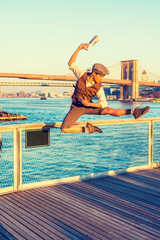 New York City Boy. Wearing newsboy cap, shirt, vest, pants, leather boot shoes, Asian American guy jumping into air at harbor in sunset, raising arm, holding newspaper, dancing with joy, excitement..