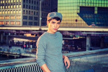 Portrait of New York City Boy. Wearing newsboy cap, knitting sweater, Asian American college student standing in business district with high buildings, looking at you. Filtered effect..