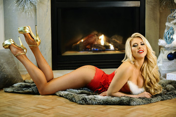 Flirty, young blond woman with  curvaceous body in red lingerie and hosiery posing sexy on a throw with fireplace on the background.