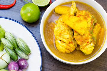 Yellow curry with Snapper fish and coconut shoot in white bowl on wooden table Thai food delicious