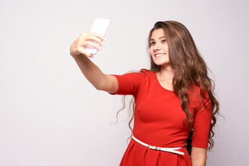 Portrait girl. Selfie on phone. Red dress