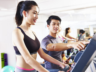 young asian woman exercising on treadmill