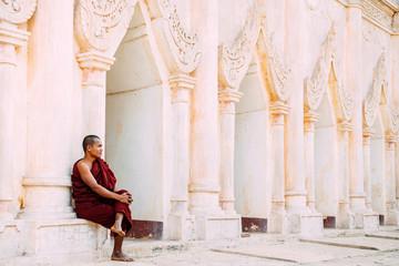 BAGAN, MYANMAR - March 6, 2017: Buddhist monk sitting near pagoda in Bagan