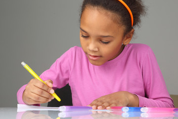 dark-skinned girl draws with crayons on paper.