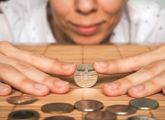 A woman plays a dirham coin. Concept plans and plan.