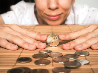 A woman plays with a coin 2 euros. The concept plans in the business plan.