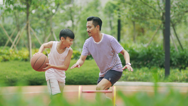 Asian father & son playing basketball in garden in morning