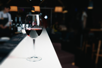 A glass of red wine close-up on a bar, white counter. Dark background.