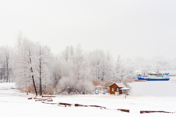 small cabin on river bank, covered with snow. winter day, in Russia. blew ship behind.