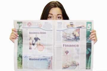 Young woman reading newspaper. Girl holding daily paper with news and looking from the side of pages. Business journal and businesslady isolated on white. Focus on eyes, blurred tabloid