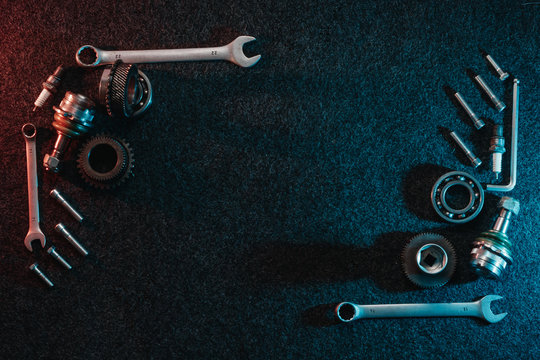 Frame of bearings, spanners, bolts on a dark background. Top view, flat design. Automotive concept.
