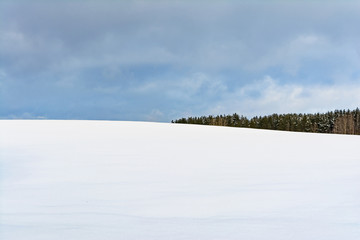 winter snowfield and cloudy sky with large clouds, winter nature