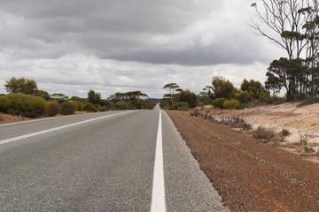 Leere Straße mit rotem Sand auf dem Seitenstreifen im Outback von West-Australien