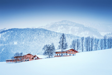 Winter landscape at early morning in Austria with snow, wooden buildings, blue sky and copy space