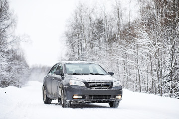 The car stands on a snow-covered road