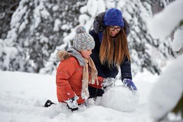 winter fun. a girl and a boy making snowballs.