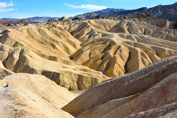 Golden badlands eroded into waves, pleats and gullies at Zabriskie Point in the Death Valley National Park.
