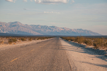 A straight road in the Death Valley National Park in the early morning - summer