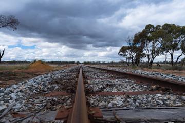 Blick über ein Bahngleis in die Ferne mit wolkigem Himmel