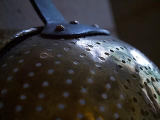 Gros plan sur un écumoire en cuivre du XVIIIe