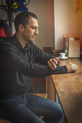 Young man in casual clothes drinks coffee while sitting in a cafe. Man drink coffee in cafe. Cozy atmosphere. Coloring and processing photo.