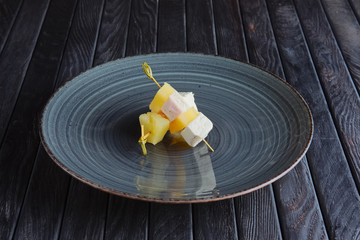Appetizer for reception. Piece of chicken fillet with mozzarella and pineapple on skewer