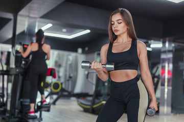 Woman lifting dumbbells in gym