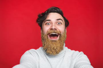 Man with winter shiny glitter in beard on red