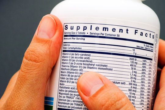 White plastic jar with supplement facts of multivitamins in person hands.
