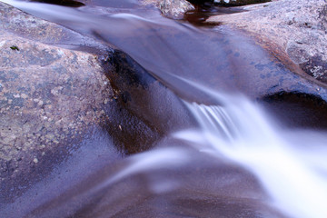 Macro Blurred Motion and Slow Shutter Speed Water Fall Photography over Stone.