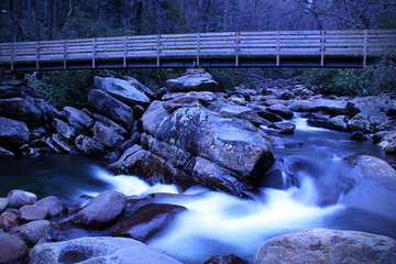 Slow Shutter Speed River Photography of a Small Waterfall with a Wooden Walk Way Bridge over the River.