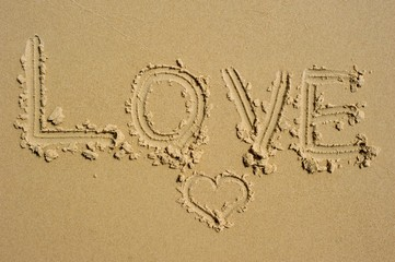 "Summer love! The word ""love"" is written in the sand, in all caps, with a little heart underneath it."