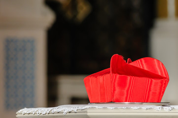 A cardinal's Beretta hat sits on a table during a requiem mass