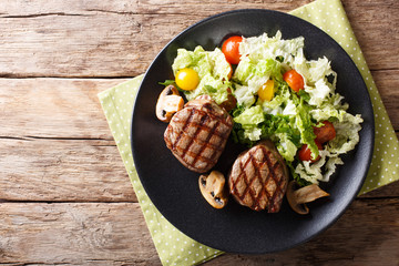 Healthy food: filet mignon steak with mushrooms and vegetable salad close-up. Horizontal top view