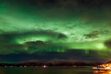 Amazing Aurora Borealis in the clouds in North Norway above the mountains and the sea, Tromso City