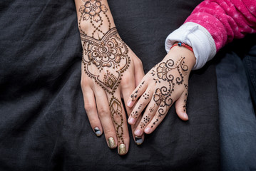 Picture of human hand being decorated with henna