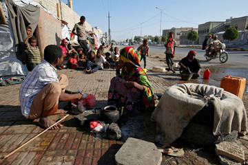 People displaced by the war in the northwestern areas of Yemen go about their day outside their makeshift huts on a street in the Red Sea port city of Hodeida