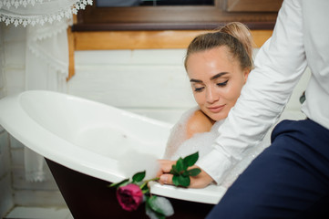 Young and beautiful woman relaxing in the bath with man
