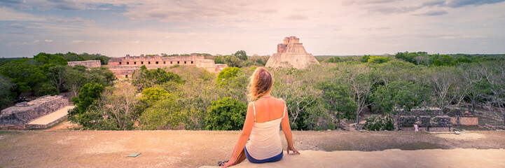 Girl sitting on the top of the Chichen Itza city in Mexico