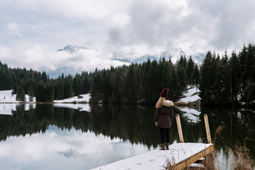 Young female standing at Lake Geroldsee overlooking a forest with cabin with the Karwendel Mountains in Background in Bavaria, Germany in winter