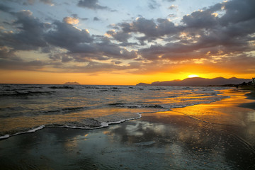 Scenic colorful sunset at the sea coast with dramatic clouds over the Mediterranean sea. Summer sunset.