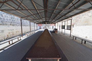 Langer Tisch unter schattenspendender Überdachung im Innenhof eines Gefängnis