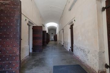 Blick in einen Gefängnis-Zellentrakt mit teilweise geöffneten Massivholztüren / Zellen