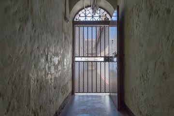 Gang mit verschlossener Metalltür als Durchgang zum Gefängnis-Innenhof einer Haftanstalt