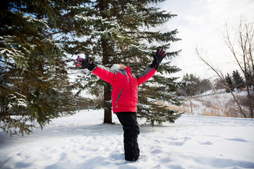 Child enjoying outdoor winter season with arms wide open.