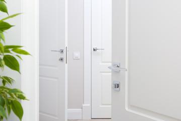 Modern chrome door handle on white door. Beautiful interior closeup