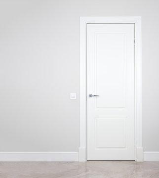 Modern white door. Grey wall with free space. Minimalist bright interior