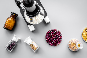 Food analysis process. Rice under microscope, red beans and wheat in petri dishes on grey background top view copyspace